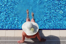 Woman In Bikini And Sun Hat Sitting On The Edge Of Swimming Pool And Dangling Her Legs In Water, Top View. Summer Vacation On Beach Resort, Tanning And Leisure Concept