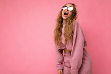 Attractive Positive Overjoyed Young Blonde Woman Wearing Everyday Stylish Clothes And Modern Sunglasses Isolated On Colorful Background Wall And Having Fun