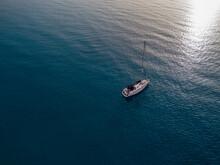 Aerial View Of A Sailboat Moored Off The Coast Of Calabria In Tropea. Italy. Tyrrhenian Sea. Coastline And Blue Sea