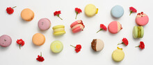 Baked Macarons With Different Flavors And Rosebuds On A White Background