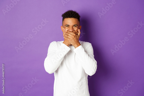 Photo Image of shocked and disgusted african-american man, cover mouth, refrain from v