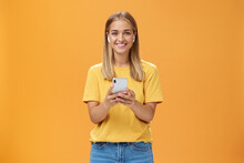 Portrait Of Friendly Charismatic And Outgoing Good-looking Young Female In Yellow T-shirt Holding Smartphone Wearing Wireless Earphones Enjoying Listening Music On Way To Fitness Gym