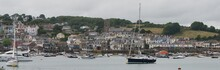 Calm Coastal Scene In Salcombe (Devon, UK) On A Grey Day. Moored Boats (yachts, Sailing Boats, Cruisers, Lifeboat, Dinghies) In The Harbour, A Church And Colourful Houses Above The Quayside