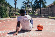 Rear View Of A Black Afro Boy Using His Cell Phone And Listening To Music With Headphones On The Basketball Court. Concept Technology And Sport.