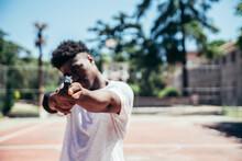 Black African American Boy On A Basketball Court Aiming A Gun At Camera. Focus On The Gun.