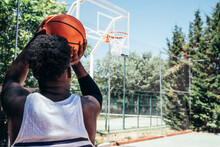 Rear View Of An African-American Black Boy Ready To Shoot The Ball Into The Basket.