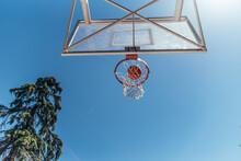 Bottom View Of A Basketball Basket. Ball Entering Through The Hoop.