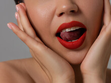 Close-up Of Sexy Female Lips With Tongue. Clean Skin And A Clear Lip Contour Are Outlined With A Fashionable Red Lipstick. White Teeth And The Beauty Of Smile For Stamotologii, Spa Or Cosmetology