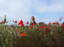 Portrait Of Woman With Hat Standing Among Green Grass And Red Flowers