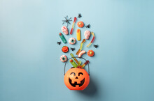 Various Halloween Sweets And Candies In A Pumpkin Pot Top View On Blue Solid Background