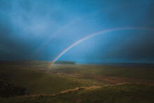 An Aerial View Of A Double Rainbow Filling A Dark Blue Sky.