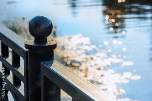 Vászonkép Fencing on the embankment overlooking the reflection of the sun in the water