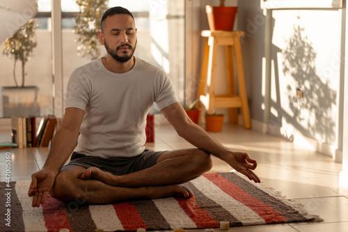 Fotografie, Tablou Joven se dispone en su hogar a hacer ejercicios de estiramiento relajación y yog