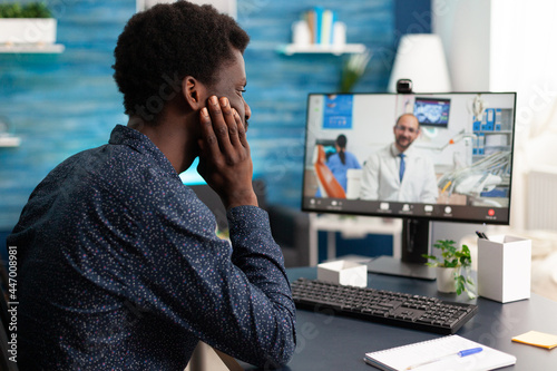 Fotografía Healthcare consultation of african american guy talking to doctor using video call app sitting at home