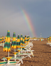 Rainbow Emerging From The Beach With Many Closed Sunshades After The Storm
