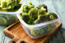 Containers With Frozen Broccoli On Color Wooden Background