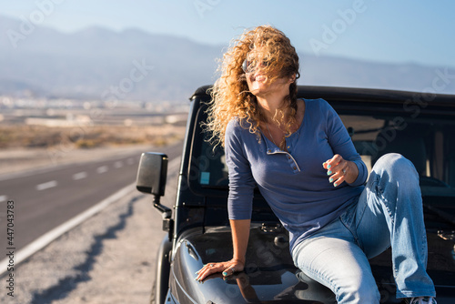 Obraz na plátně Cheerful happy, lady sitting on the car in travel adventure vacation smile and e