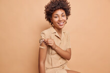 Indoor Shot Of Positive Dark Skinned Woman With Curly Hair Shows Vaccinated Arm With Plaster Gets Second Dose Of Vaccine Happy To Feel Protected Raises Sleeve Of Dress Isolated Over Beige Background