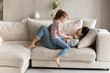 Leinwandbild Motiv Small ethnic girl child and excited young Latino mom relax on couch in living room feel playful on weekend together. Overjoyed Hispanic mother and little daughter have fun play and tickle at home.