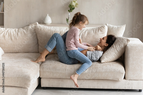Photographie Small ethnic girl child and excited young Latino mom relax on couch in living room feel playful on weekend together