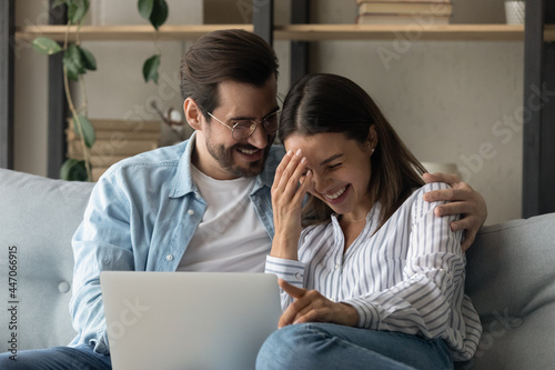 Fényképezés Cheery young 30s couple resting on sofa in living room with laptop, laugh on funny internet content joking enjoy free time using internet fun read amusing media news