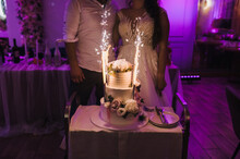 A Large Two-tiered Cream Cake With Fireworks Stands On The Table On A Wedding Evening In A Restaurant Against The Backdrop Of Newlyweds In The Dark.