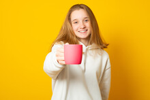 Portrait Of Young Woman Giving Hot Coffee Or Tea Beverage To Camera On Yellow Background.