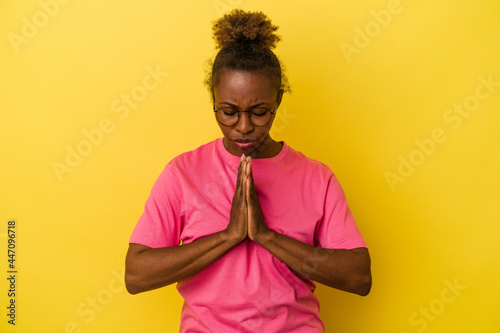 Fotografiet Young african american woman isolated on yellow background praying, showing devotion, religious person looking for divine inspiration