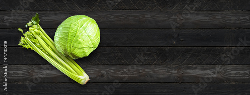 Canvas Celery branch bunch and green cabbage isolated on black wood banner