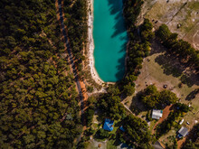 Top View Shot Of A Blue Lake Surrounded By Trees And Houses On A Sunny Day