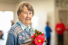 Smiling Elderly Woman Holding Camellia Flowers