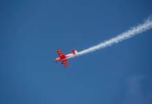 The Red Plane Makes A Difficult Turn Leaves A White Trail Of Flight Against The Background Of The Sky