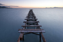 Wooden Pier Or Jetty Remains On A Blue Lake Sunset.