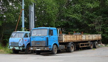Two Old Rusty Abandoned Trucks With Blue Cabs, Oktyabrskaya Embankment, St. Petersburg, Russia, July 2021