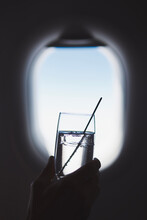 Passenger Enjoy Drink During Flight. Man Holding Glass Of Gin And Tonic Against Airplane Window.