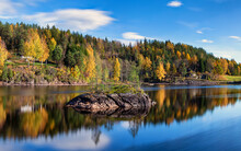 Long Exposed Panorama Landscape Of Gold  Colorful Fall Time By The Lake Tokke In Telemark Region. Blue Sky . Nice Reflection Of Little  Stone Island In Lake Water. Autumn In Norway.
