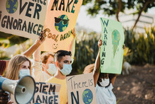 Young People Protesting For Climate Change While Wearing Safety Masks Outdoor In The City - Focus On Gay Man Face