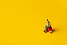 Miniature Figure Of Man Sits On Christmas Bauble On Yellow Background
