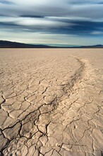 Dry Cracked Earth In The Desert And Mountains Background Blue Sky