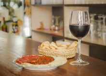 Glass Of Red Wine With Bread And A Plate Of Cheese And Morcilla On A Wooden Table, Spanish Tapa