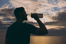 Side Profile View Young Strong Sporty Fit Sportsman Man 20s Wear Sports Clothes Warm Up Training Drink Still Water Hold Bottle At Sunrise Sun Dawn Over Sea Beach Outdoor Seaside In Summer Day Morning.