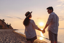Back View Young Happy Lovely Couple Two Friends Family Man Woman 20s In Summer Clothes Hold Hands Walking Stroll Together At Sunrise Over Sea Beach Ocean Outdoor Exotic Seaside In Summer Day Evening.