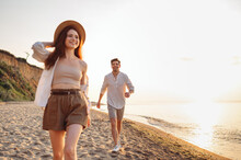 Full Body Smiling Happy Fun Young Couple Two Friends Family Man Woman 20s Wearing Casual Clothes Hold Hands Walk Together At Sunrise Over Sea Beach Ocean Outdoor Exotic Seaside In Summer Day Evening.