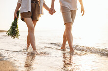 Cropped Close Up Young Couple Two Family Man Woman In White Clothes Hold Flowers Bouquet Hand Walk In Water Waves Together At Sunrise Over Sea Beach Ocean Outdoor Seaside In Summer Day Sunset Evening.