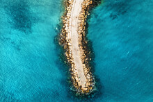 Aerial Top Down View Of Stone Breakwater In Bright Blue Sea Surface.