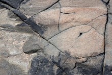 Seaside Rock Face With Cracks And Sand