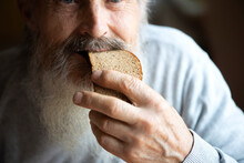 Old Sad Man With A Long Gray Beard Sitting By The Table And Eating Bread