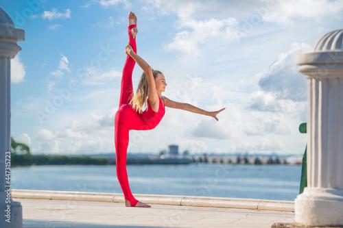 Gymnast teenage girl in red suit posing on embankment against background of the Tapéta, Fotótapéta