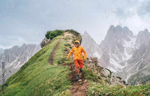 Fototapeta premium Dressed bright orange soft shell jacket backpacker running by green mountain path with picturesque Dolomite Alps range background,. Active people and European mountain hiking tourism concept image.