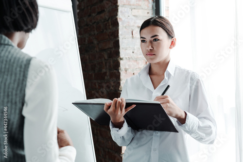 Fototapeta Asian girl student in a white shirt holds a notebook in her hands and writes dow
